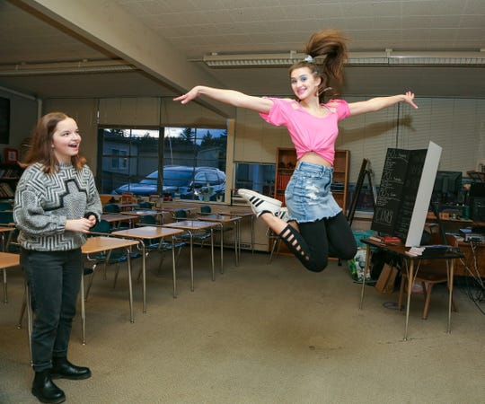 """Central Kitsap Middle School student Tegan Arthur shows off her 1980s-inspired outfit as student Sarah Witham watches at """"Central Kitsap Middle School Through the Decades."""" The middle school held the event as students and staff prepare to move to a new building after spring break."""
