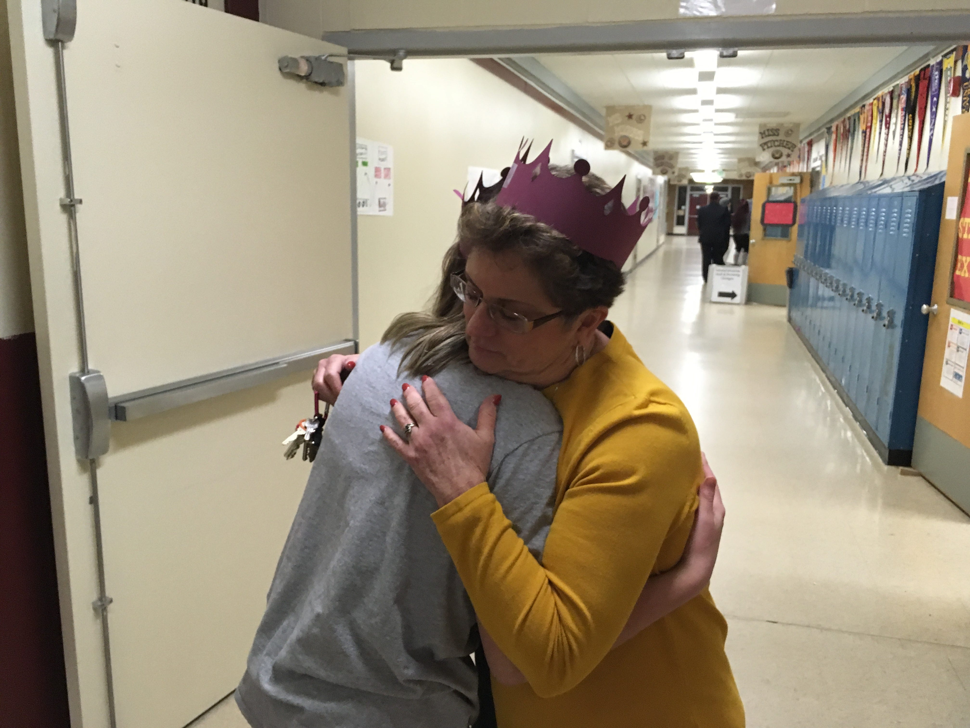 "Central Kitsap Middle School counseling secretary Linda Roberts accepts a hug and a paper crown from student Lara Charters at ""Central Kitsap Middle School Through the Decades"" on Feb. 26, 2019. The school, built in 1959, will be demolished this spring. Students will move to a new middle school building after spring break."