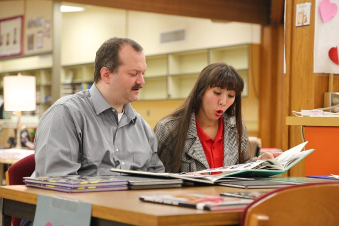 """Central Kitsap Middle School alumnus Leif Morgensen, left, who attended in the 1980s, looks over an old yearbook during """"Central Kitsap Middle School Through the Decades"""" on Feb. 26, 2019. The school, built in 1959, will be demolished this spring."""