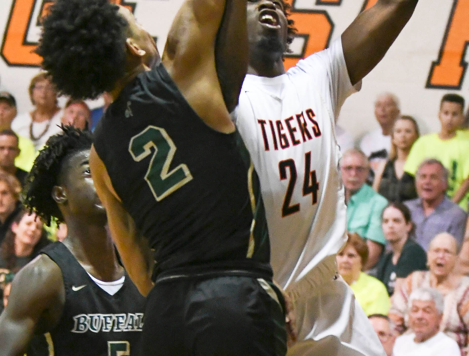 Cocoa's Marquise Freeman (24) shoots over the block of Tre Mann of The Villages during Friday's basketball Regional Final in Cocoa