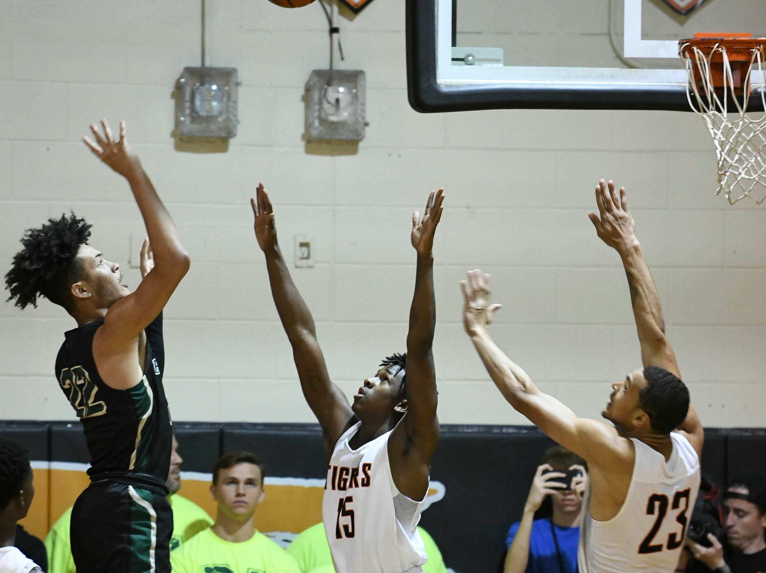 Brandon Farmer of The Villages shoots over the defense of Latrell Pad and Joseph Cartwright during Friday's basketball Regional Final in Cocoa