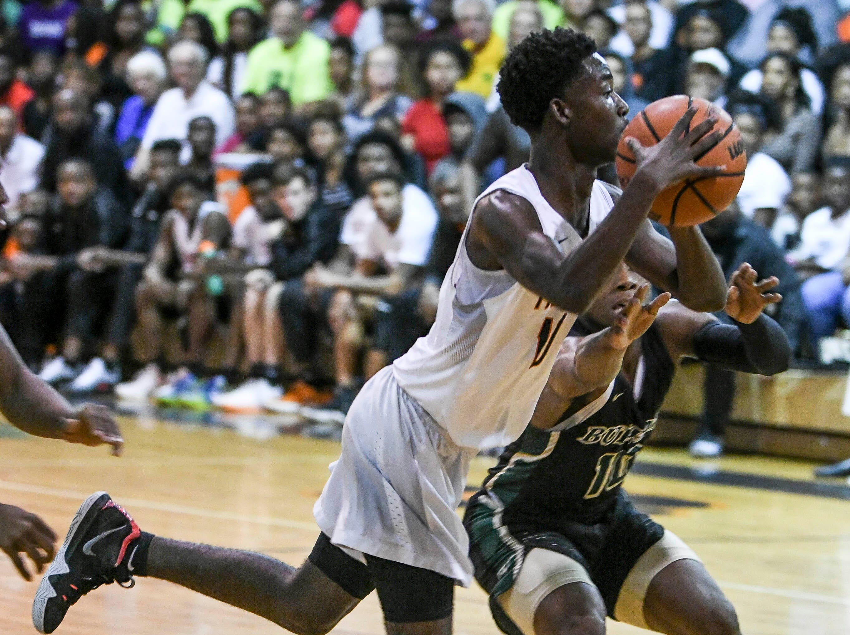 Cocoa's Samarion Bryant tries to shoot around the guard of Tre Mann of The Villages during Friday's basketball Regional Final in Cocoa