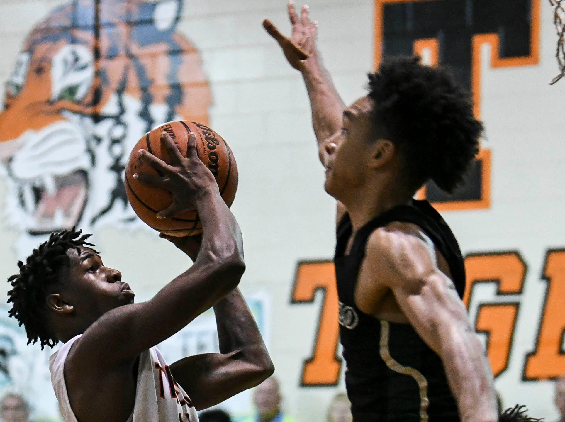 Cocoa's Latrell Pace (15) tries to shoot around the block of Brandon Farmer of The Villages during Friday's basketball Regional Final in Cocoa