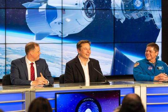 At center, SpaceX CEO Elon Musk speaks to the press during a post-launch briefing at Kennedy Space Center. At left is NASA Administrator Jim Bridenstine; at right, Astronaut Bob Behnken.