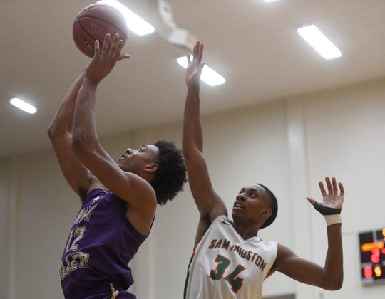Miller's Xavier Callandret, left, goes for a lay up while Sam Houston's Aviar Smith guards in the Region IV-5A boys basketball game, Friday, March 1, 2019, in San Antonio.
