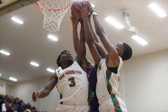 Sam Houston's De Angeles Reed, left, reaches for the rebound in the Region IV-5A boys basketball game against Miller, Friday, March 1, 2019, in San Antonio. Miller won, 69-67.