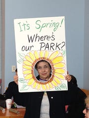 Despite her sunny sign, Camden resident Marianna Emanuele cq protests delays in opening Gateway Park along the Admiral Wilson Boulevard in Camden at a Delaware River Port Authority in 2014. The park is finally to open March 11.