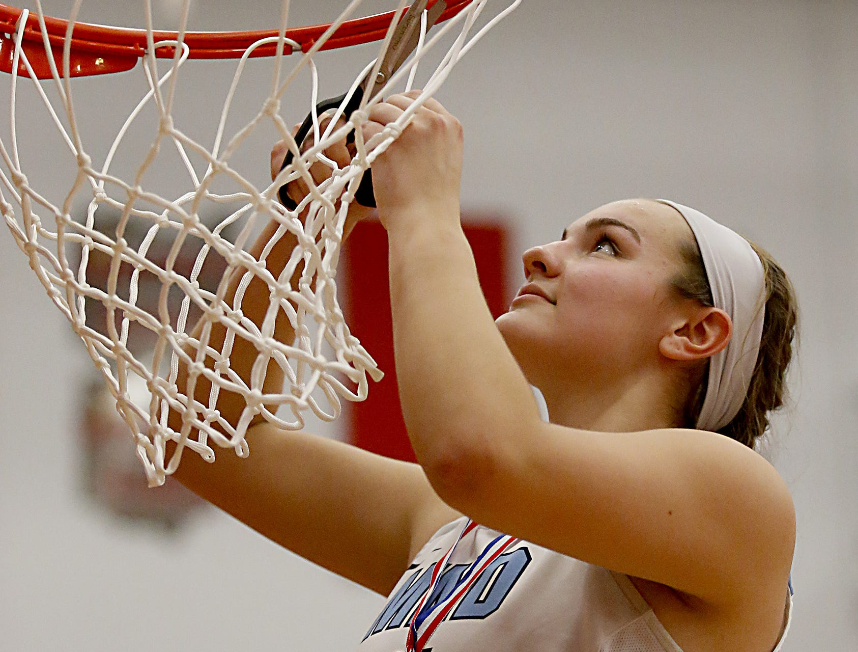 Mt. Notre Dame's Rachel Wiehe cuts the net after defeating Kettering Fairmont in their Southwest District Girls Division I finals at Princeton High School in Cincinnati Saturday, March 2, 2019.