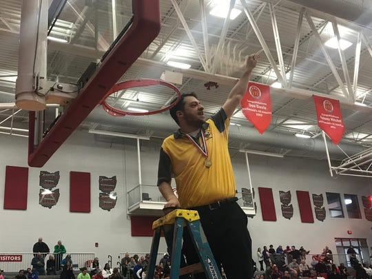 Walnut Hills head coach Adam Lazar makes the final cut on the championship net after his Lady Eagles won their second straight district title, Saturday at Princeton High School over Wayne, 58-49.