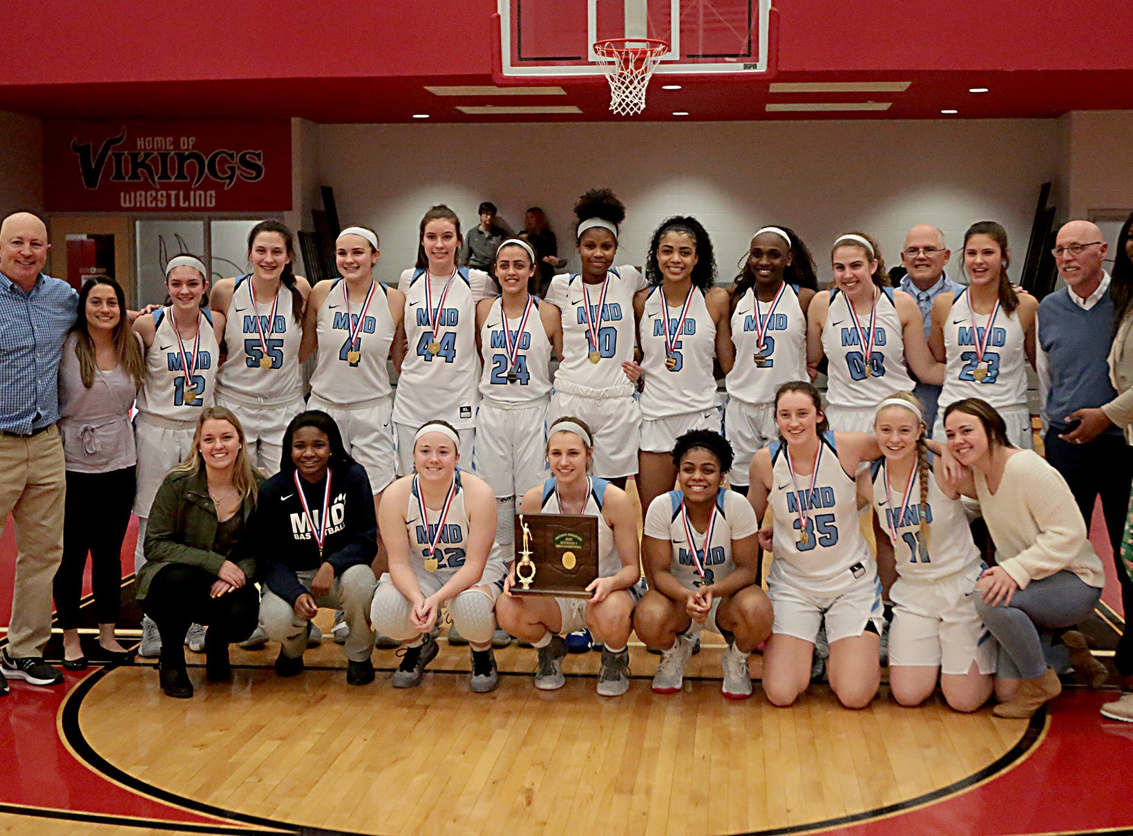 The Mt. Notre Dame girls celebrate with their trophy after defeating Kettering Fairmont in their Southwest District Girls Division I finals at Princeton High School in Cincinnati Saturday, March 2, 2019.
