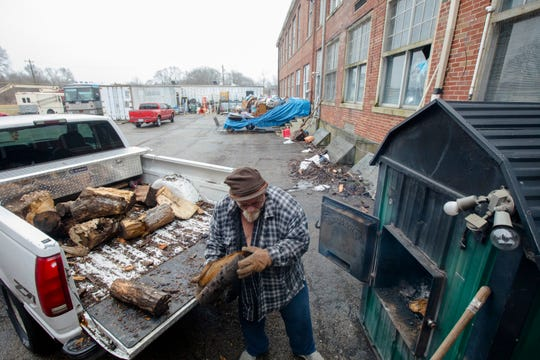 Darrell Whisman loads wood into a heater at Poasttown Elementary School, where he lives, on Tuesday, Feb. 5, 2019, in Madison Township.