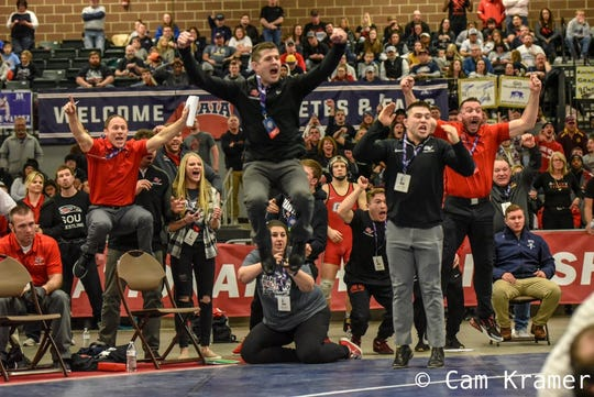 Grand View associate head coach Paul Reedy, center, and other members of the Viking coaching staff celebrate Artie Bess's pin in the quarterfinal round at the 2019 NAIA National Championships in Des Moines.