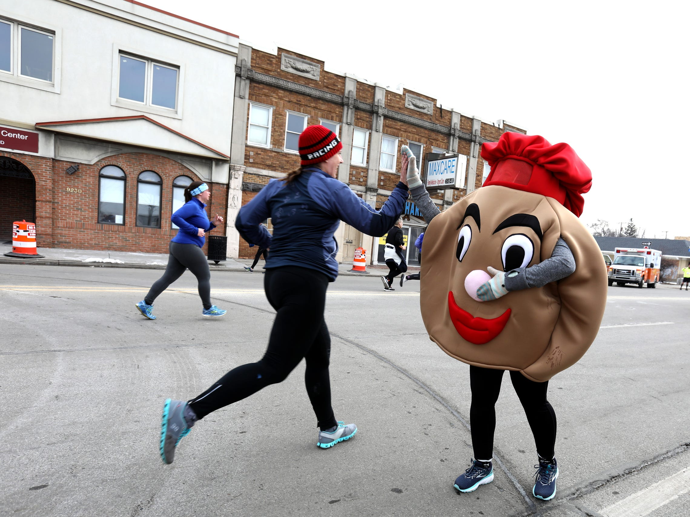 The 2019 Paczki 5K run mascot greets runners as they get close to the finish line on Joseph Campau Avenue in downtown Hamtramck on Saturday, March 2, 2019.