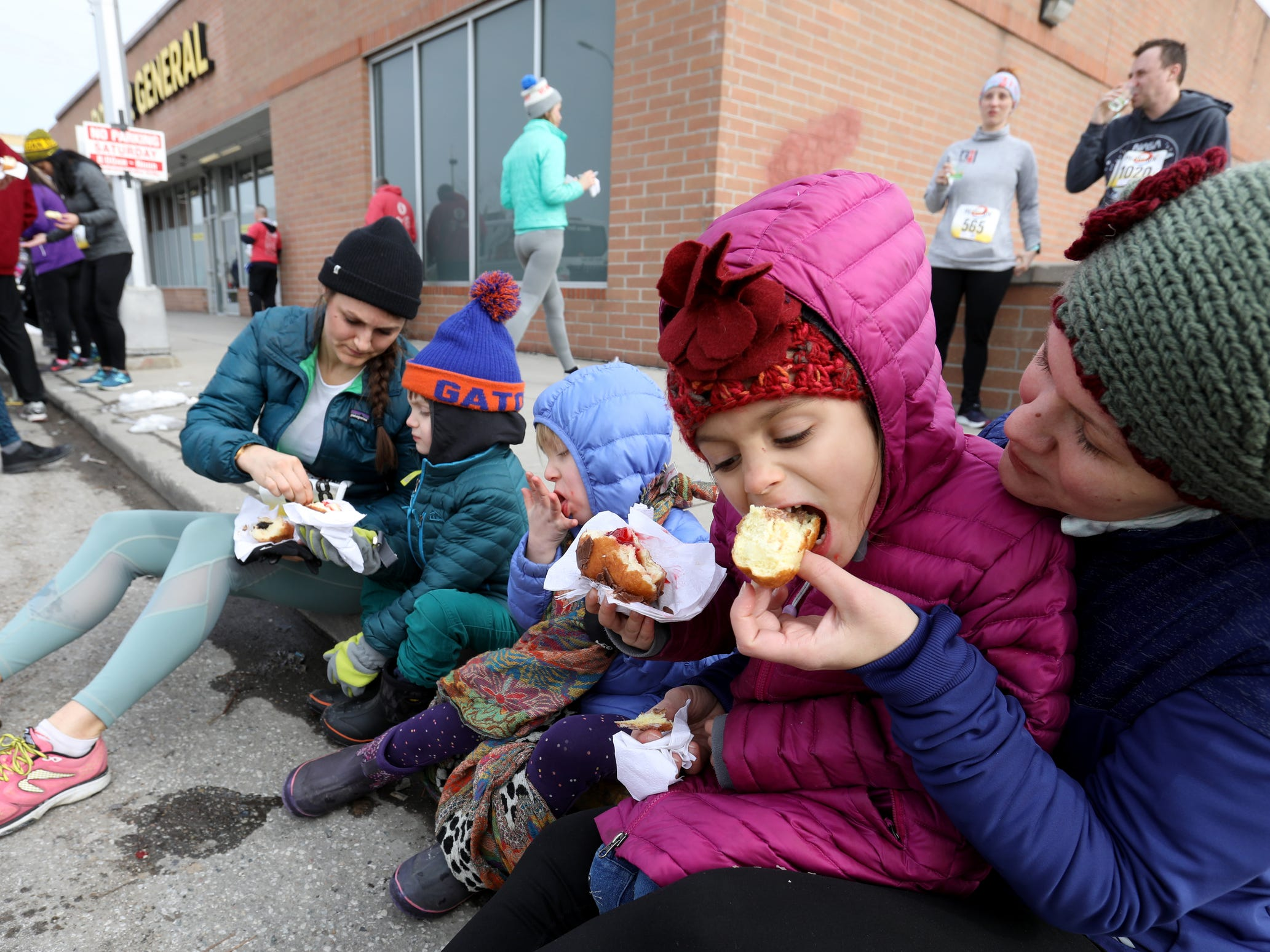 (Far right) Jennifer DeMarco, 34 of Royal Oak lets her daughter Isabella DeMarco, 6 try her Paczki after her mother had finished running the 2019 Paczki 5K run in Hamtramck on Saturday, March 2, 2019.