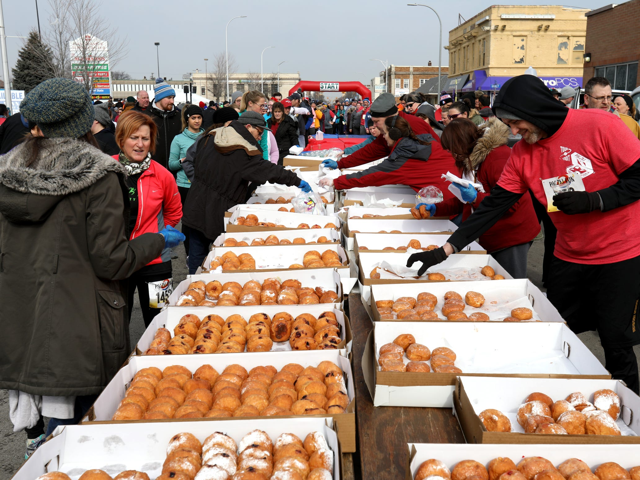 Runners look over and talk about some of the 7 variety kinds of Paczki they could choose from after they finished the 2019 Paczki 5K run through the streets and neighborhoods of downtown Hamtramck on Saturday, March 2, 2019.