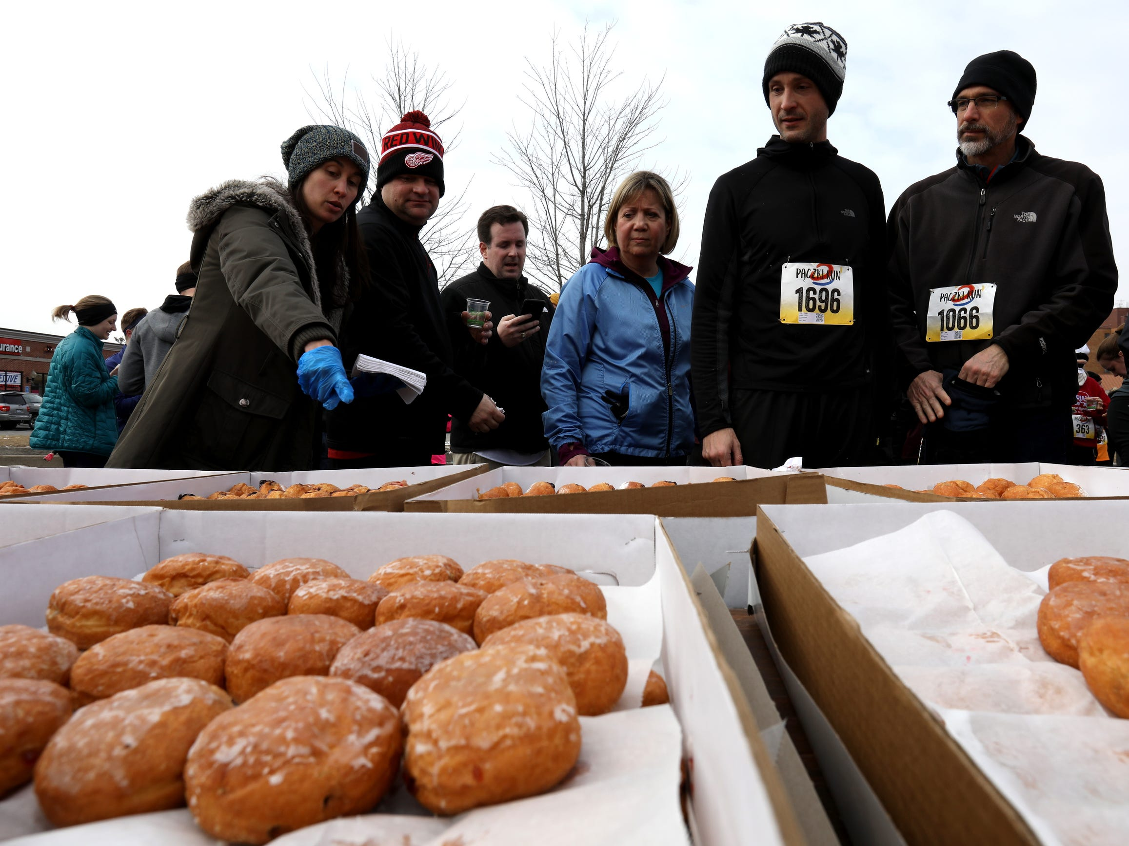 Runners look over and talk about some of the 7 variety kinds of Paczki they could choose from after they finished the 2019 Paczki 5K run through the streets and neighborhoods of downtown Hamtramck on Saturday, March 2, 2019. Two hundred and ten dozen Paczki were made for the 5k run on Saturday.