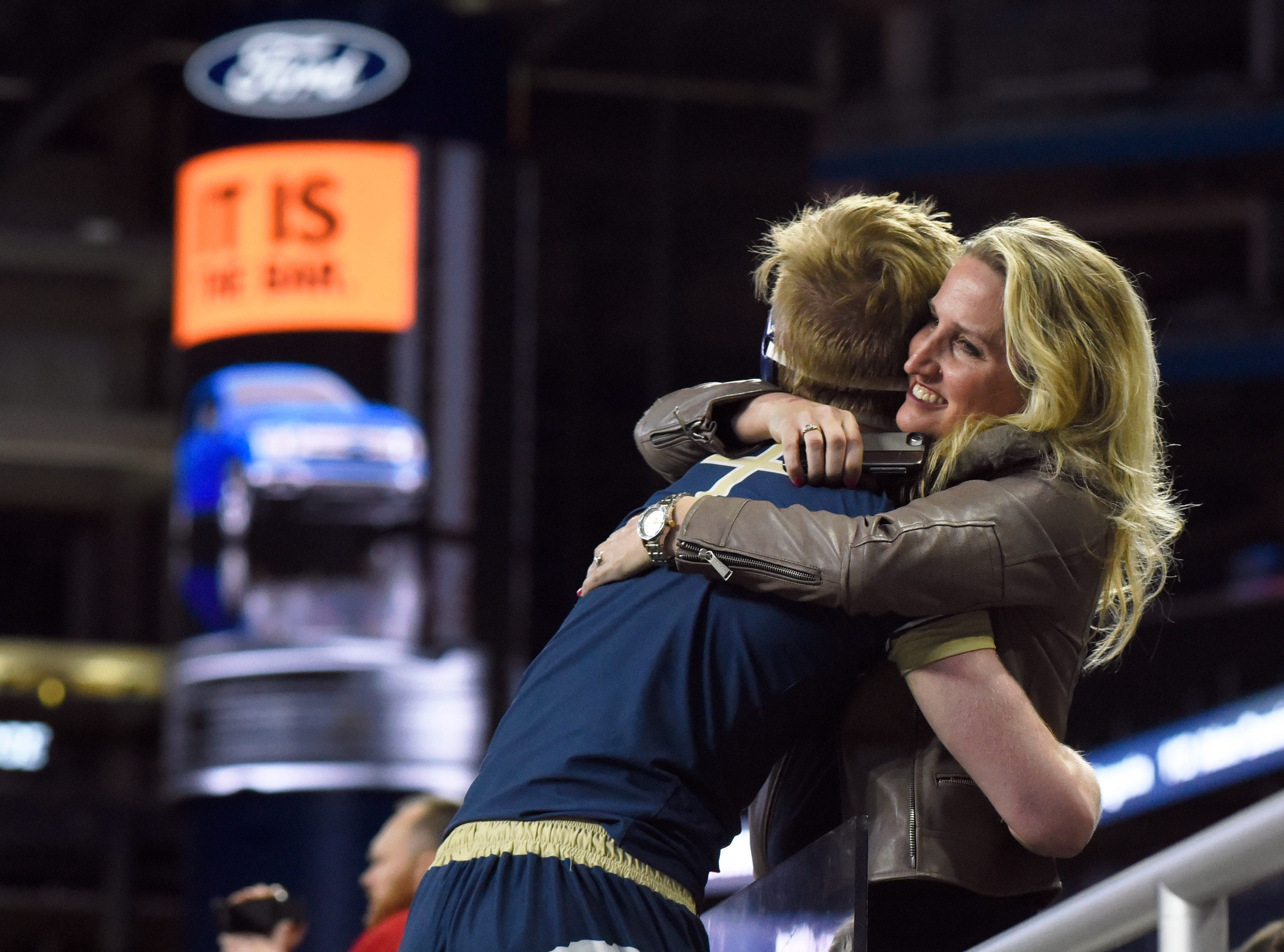 Traverse City St. Francis wrestler Brennan Nickodemus, left, is hugged by his mother, Carla Nickodemus, after Brennan won a Division 4 160-pound consolation match over Nickolas Phillips of Manchester.