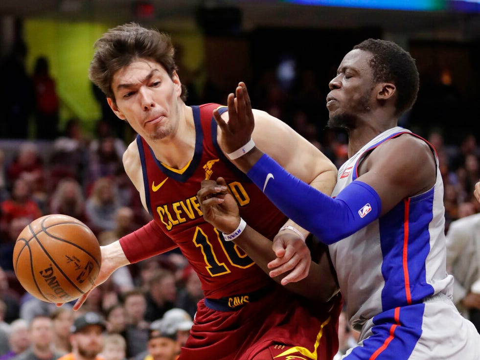 Cleveland Cavaliers' Cedi Osman, left, from Turkey, drives past Detroit Pistons' Reggie Jackson, from Italy, in the first half.