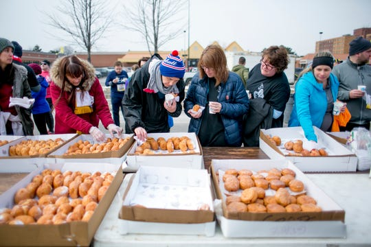 People grab post race paczkis at the 7th Annual Tour-de-Troit Paczki Run in Hamtramck, MI on March 2, 2019. (Photo by Anthony Lanzilote/Special to The Detroit News)