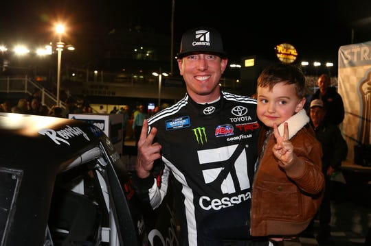 Kyle Busch poses with his son, Brexton, with the Winner's Sticker after winning the NASCAR Truck Series Las Vegas 200.