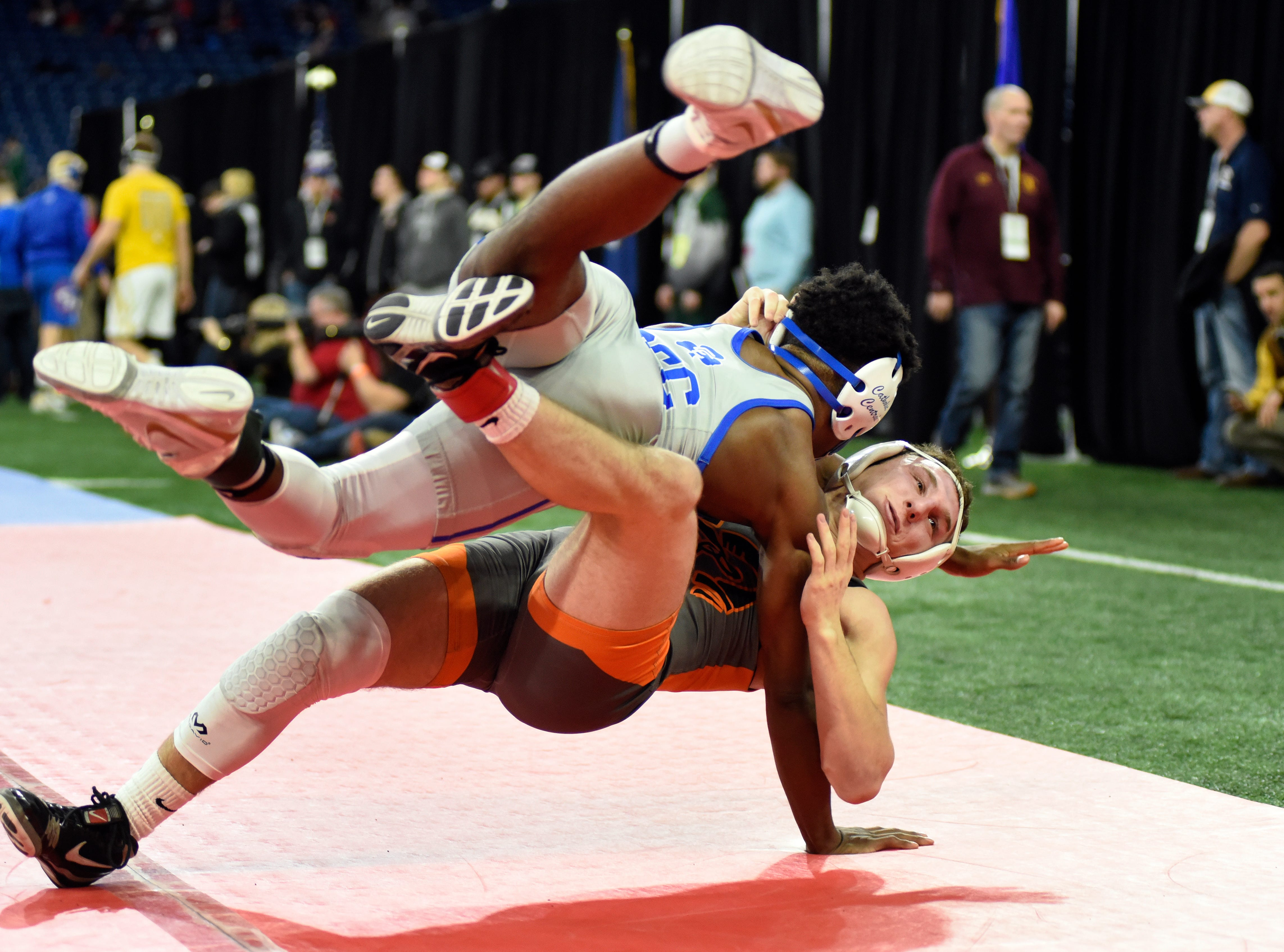Kevon Davenport of Detroit Catholic Central, top, takes down Jack Richardson of Rockford at 145 pounds in the state quarterfinals. Davenport won by pin.