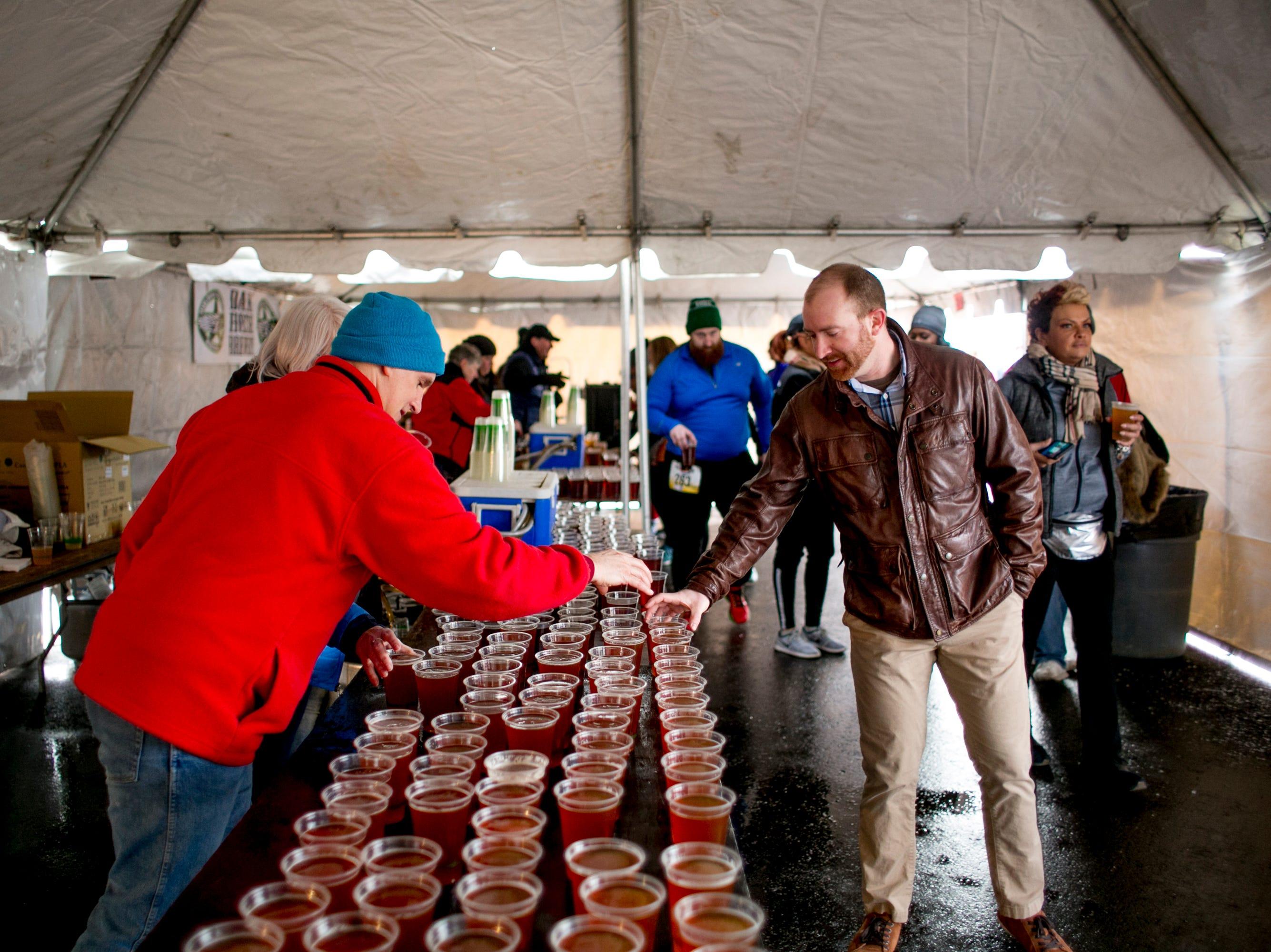 A man grabs a beer at the Paczki Run.