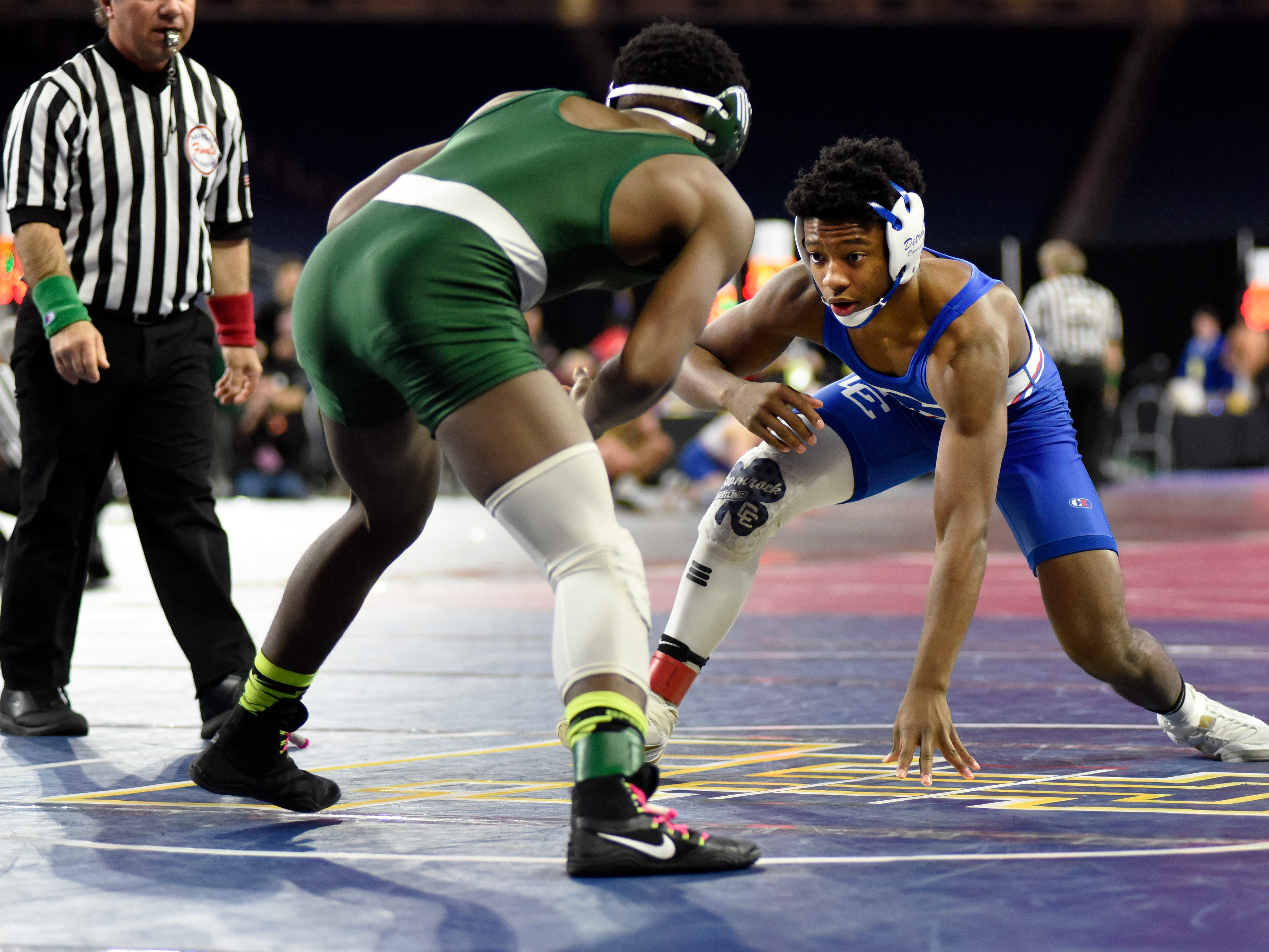 Kevon Davenport of Detroit Catholic Central, right, wrestles Damon Dunbar of Birmingham Groves in the 145 pound weight class semifinal. Davenport won by major decision over Dunbar.