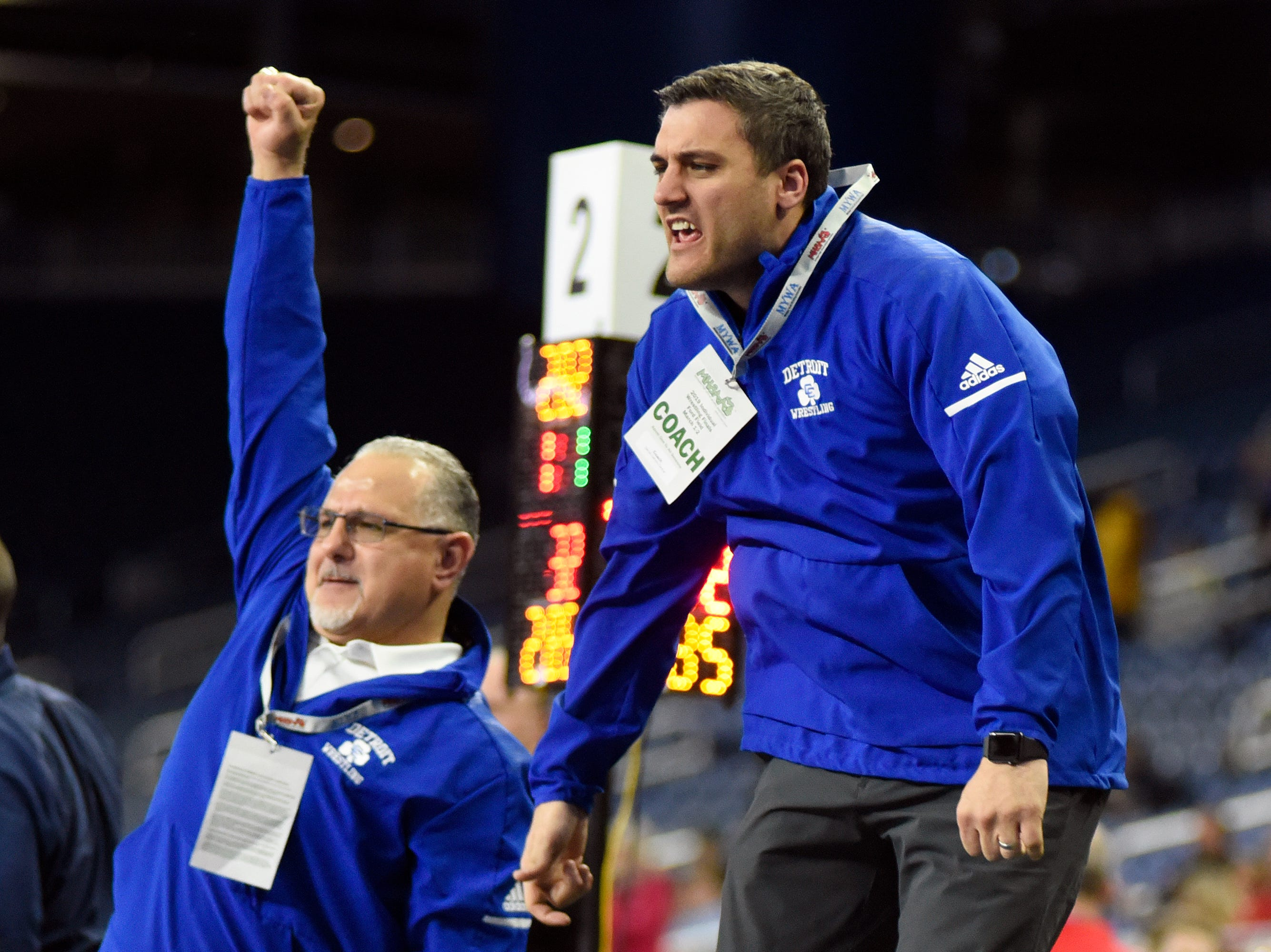 Detroit Catholic Central coaches Sam Amine, left, and Anthony Biondo react as Steven Kolcheff pins Belleville wrestler Jaden Rice in a 285-pound semifinal match.