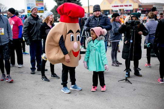 Emily Gilchrist looks at a person dressed as a paczki at the 7th annual  Paczki Run in Hamtramck on March 2, 2019.