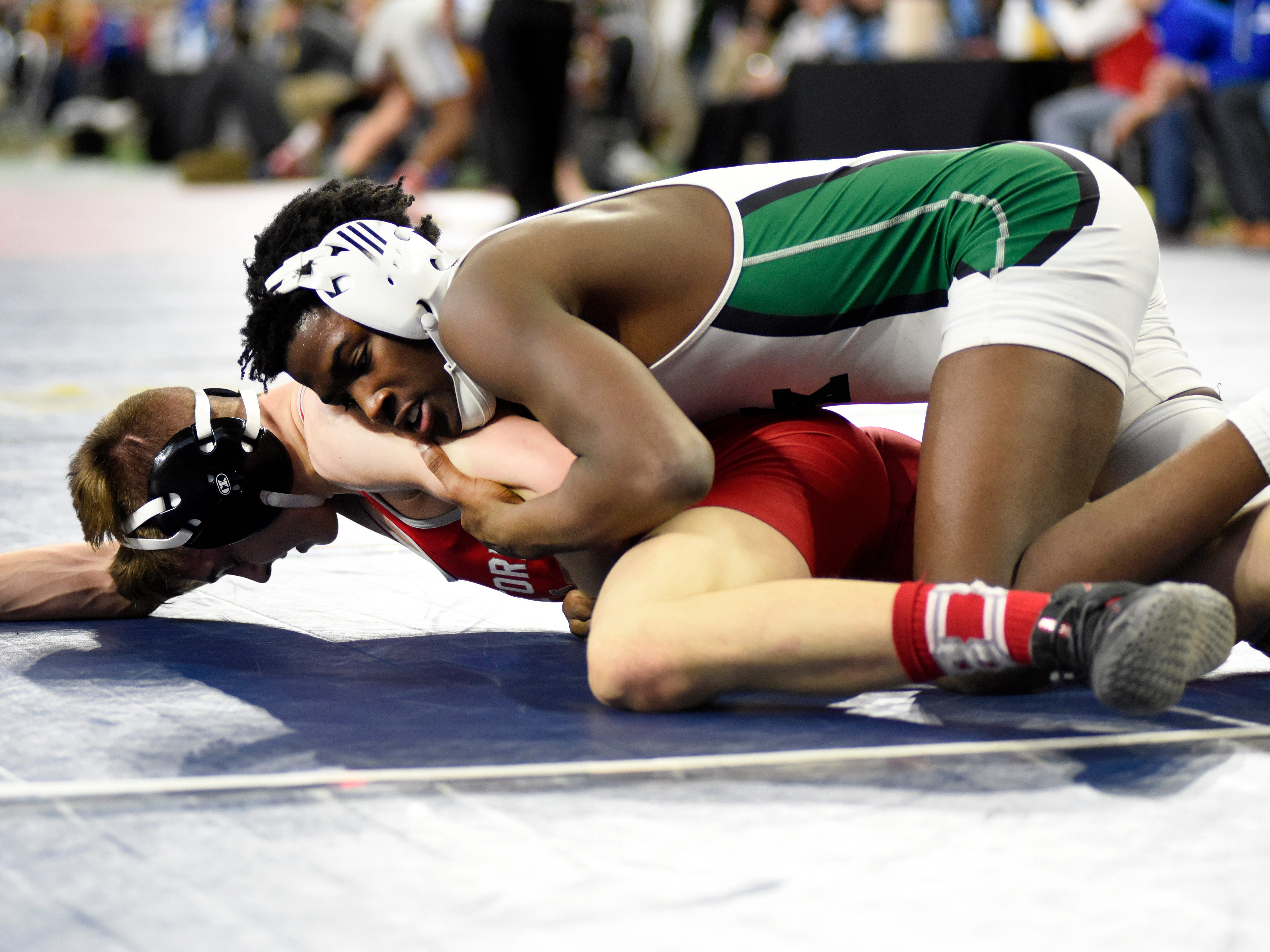 TJ Daugherty of Waterford Kettering, top, wrestles against Rollie Denker of Temperance Bedford at 130 pounds in a state quarterfinals match.