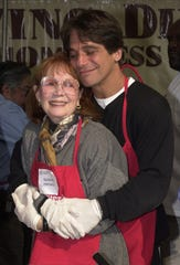 """Actor Tony Danza hugs Katherine Helmond as they prepare to help serve free dinners to the homeless at the Los Angeles Mission during """"The Great Thanksgiving Banquet"""" November 22, 2000 in Los Angeles."""