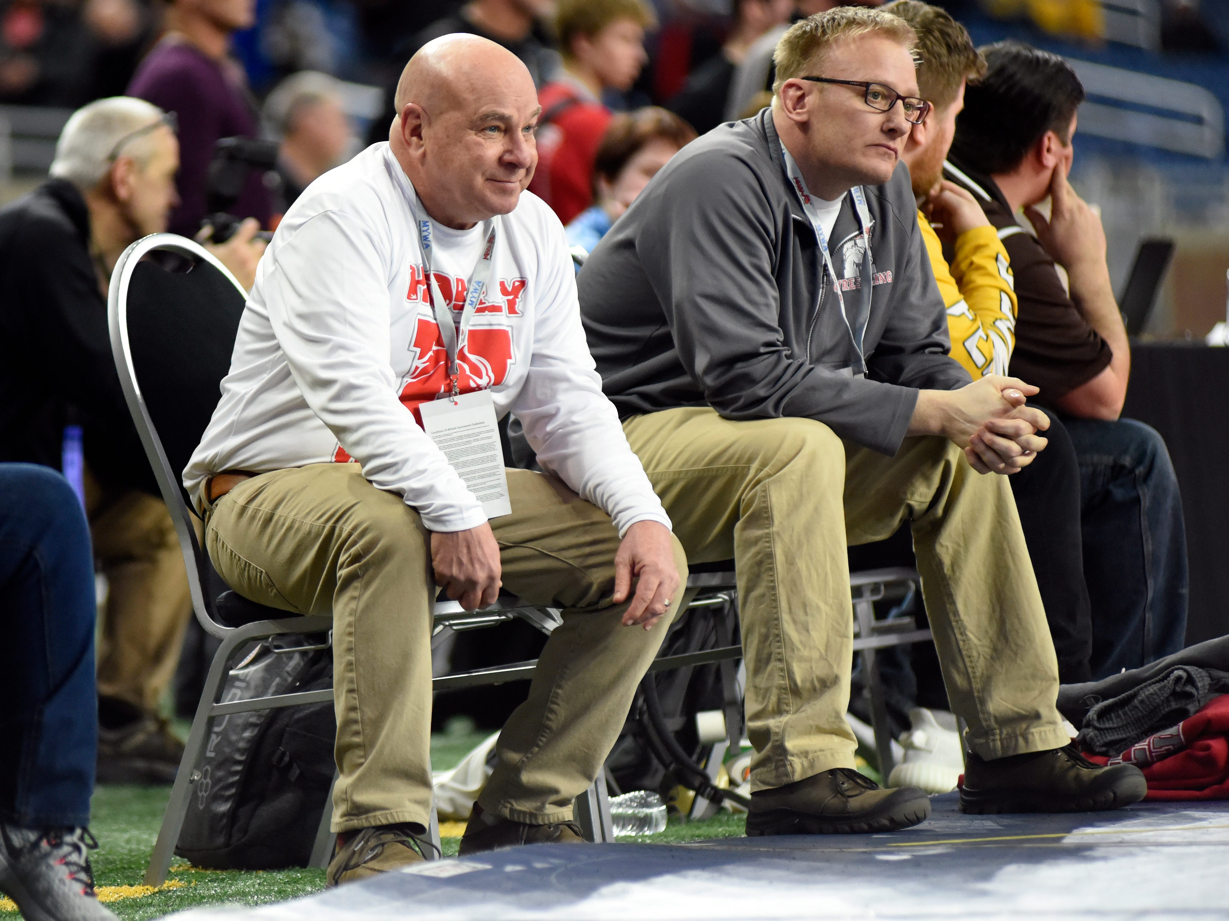 Holly High School wrestling head coach Don Pluta, left, watches his wrestlers compete in the Division 1 semifinals.