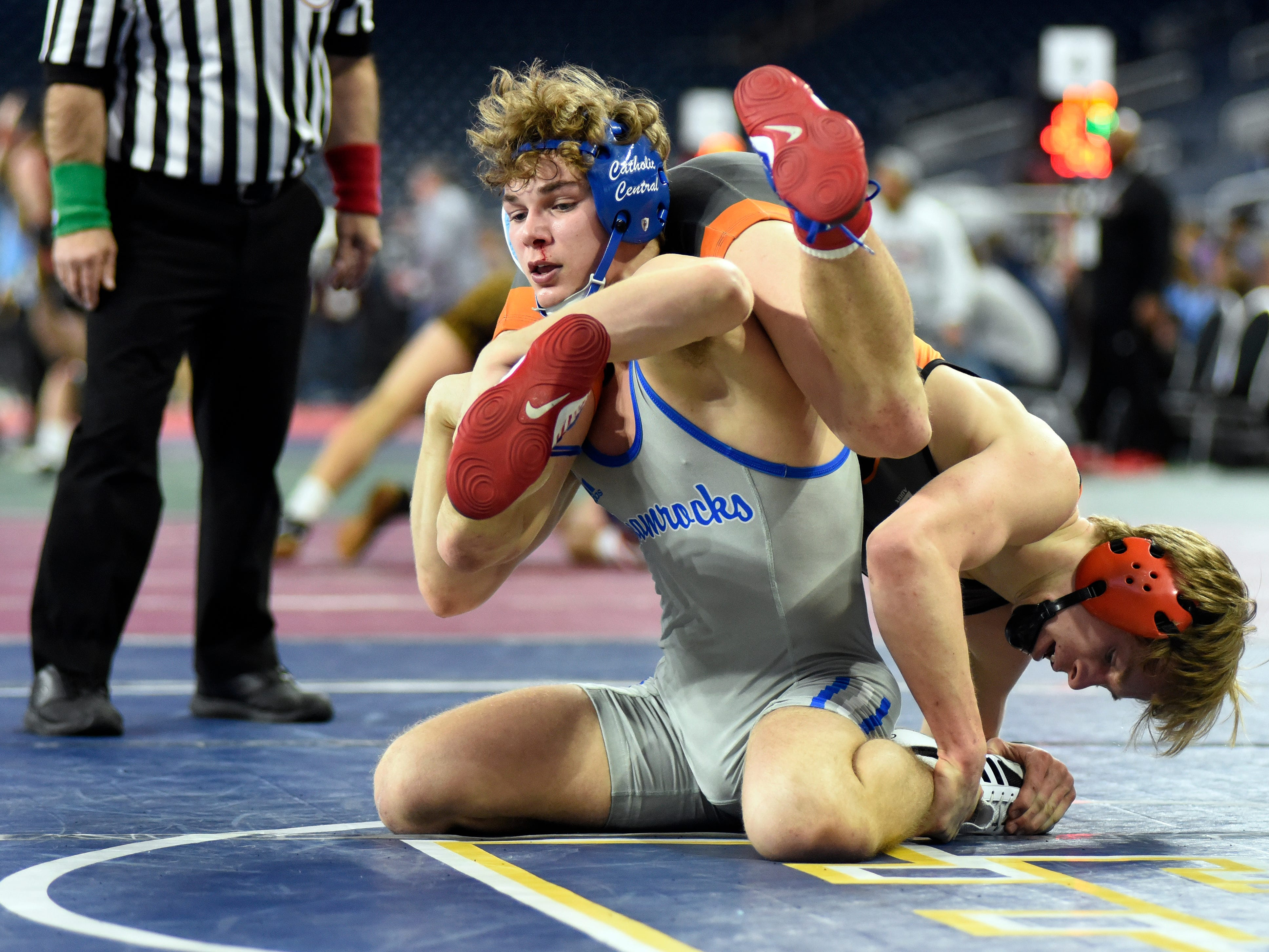 Marc Shaeffer of Detroit Catholic Central, left, wrestles Connor White of Rockford at 140 pounds, Friday, Mar. 1, 2019 during the MHSAA wrestling quarterfinals held at Ford Field in Detroit.  Shaeffer won by decision over White.