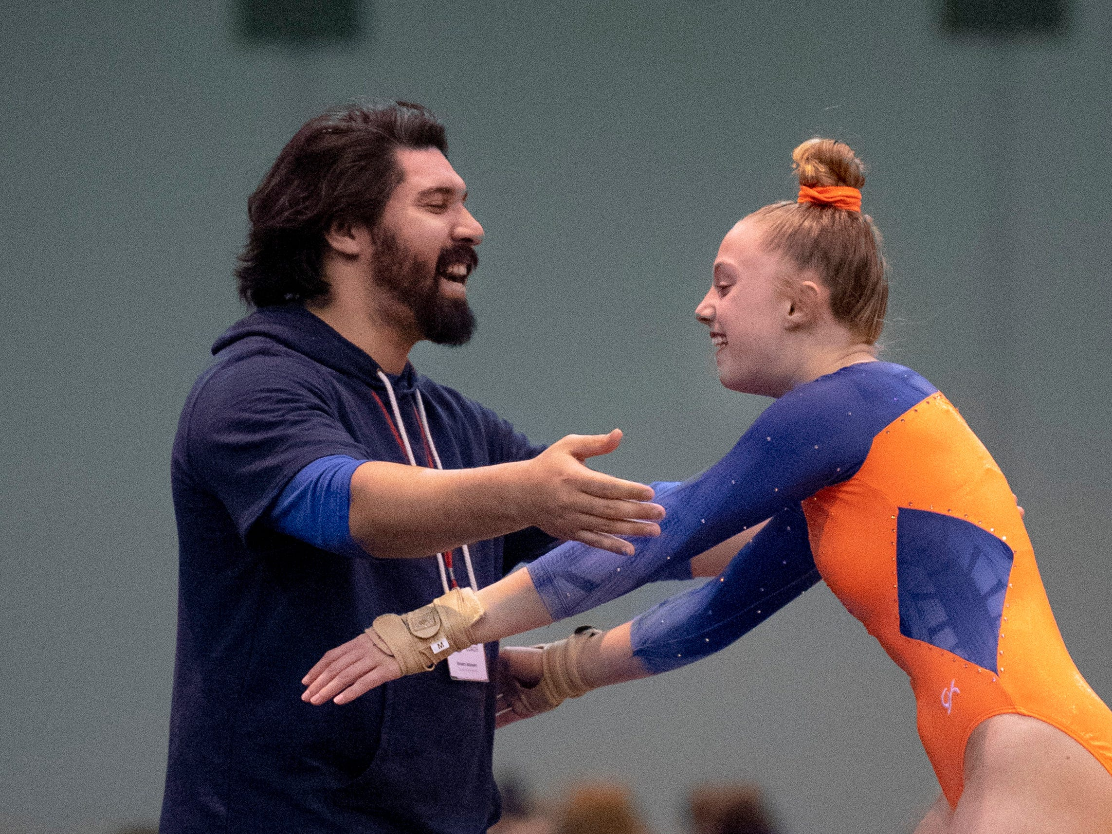 Sonshine Gymnastics coach Robert Johnson congratulates 14-year-old Sage Duggins of Holly Springs, N.C., after her final tumbling run at the VIP Classic at the Old National Events Plaza Friday afternoon.