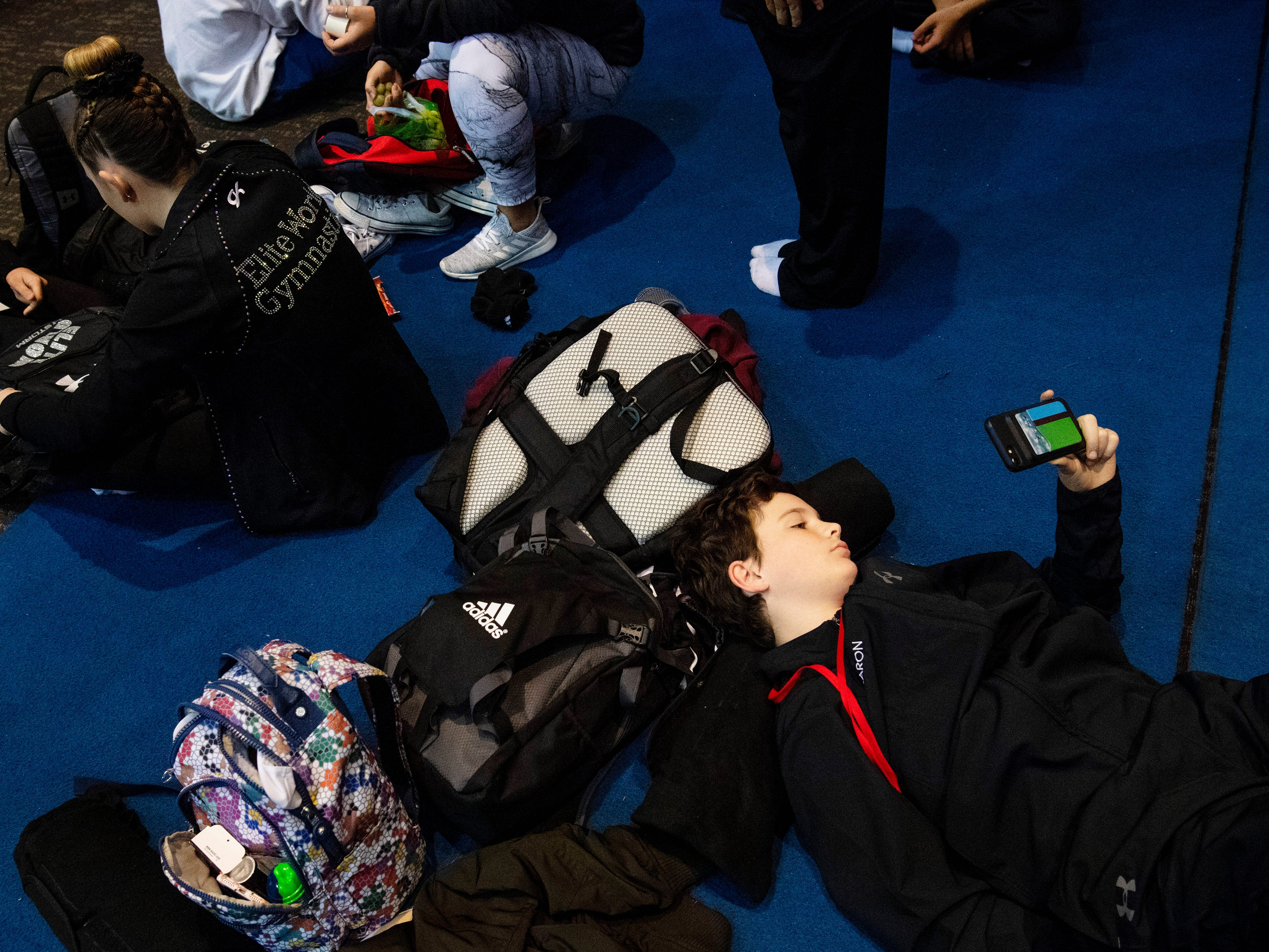 Elite Trampoline Academy team member Aaron Edelman, 12, of Westchester, N.Y., takes in a movie between competitions at the VIP Classic at the Old National Events Plaza Friday afternoon.