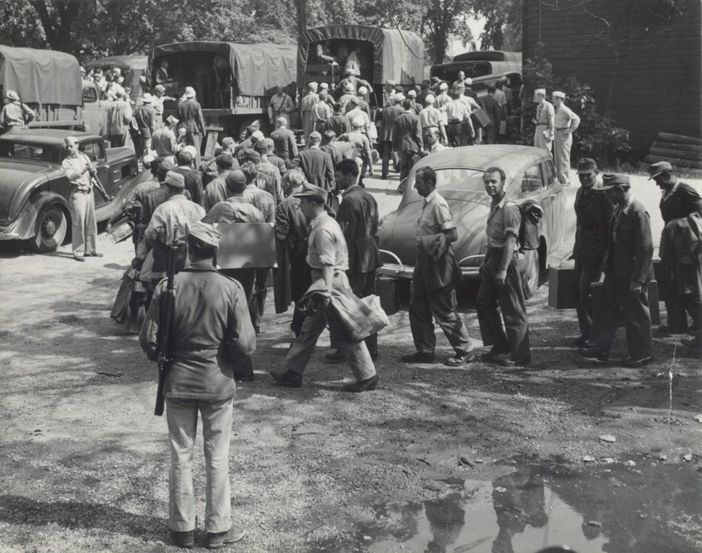 German POWs are loading onto trucks for transport to work in Door County orchards during World War II.