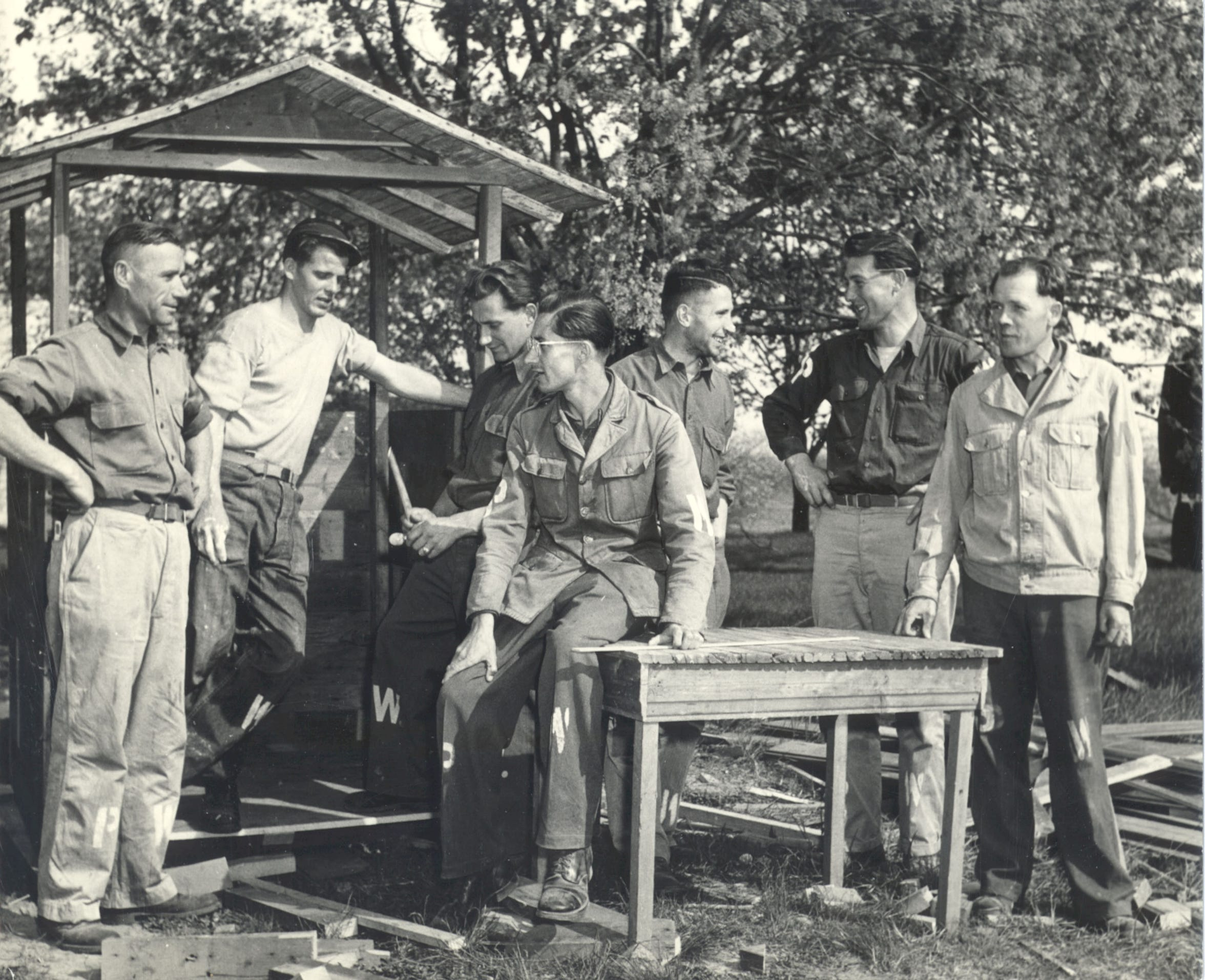 German prisoners of war talking around a table in Door County during World War II. POWs helped harvest cherries and worked in canneries because of a shortage of workers.