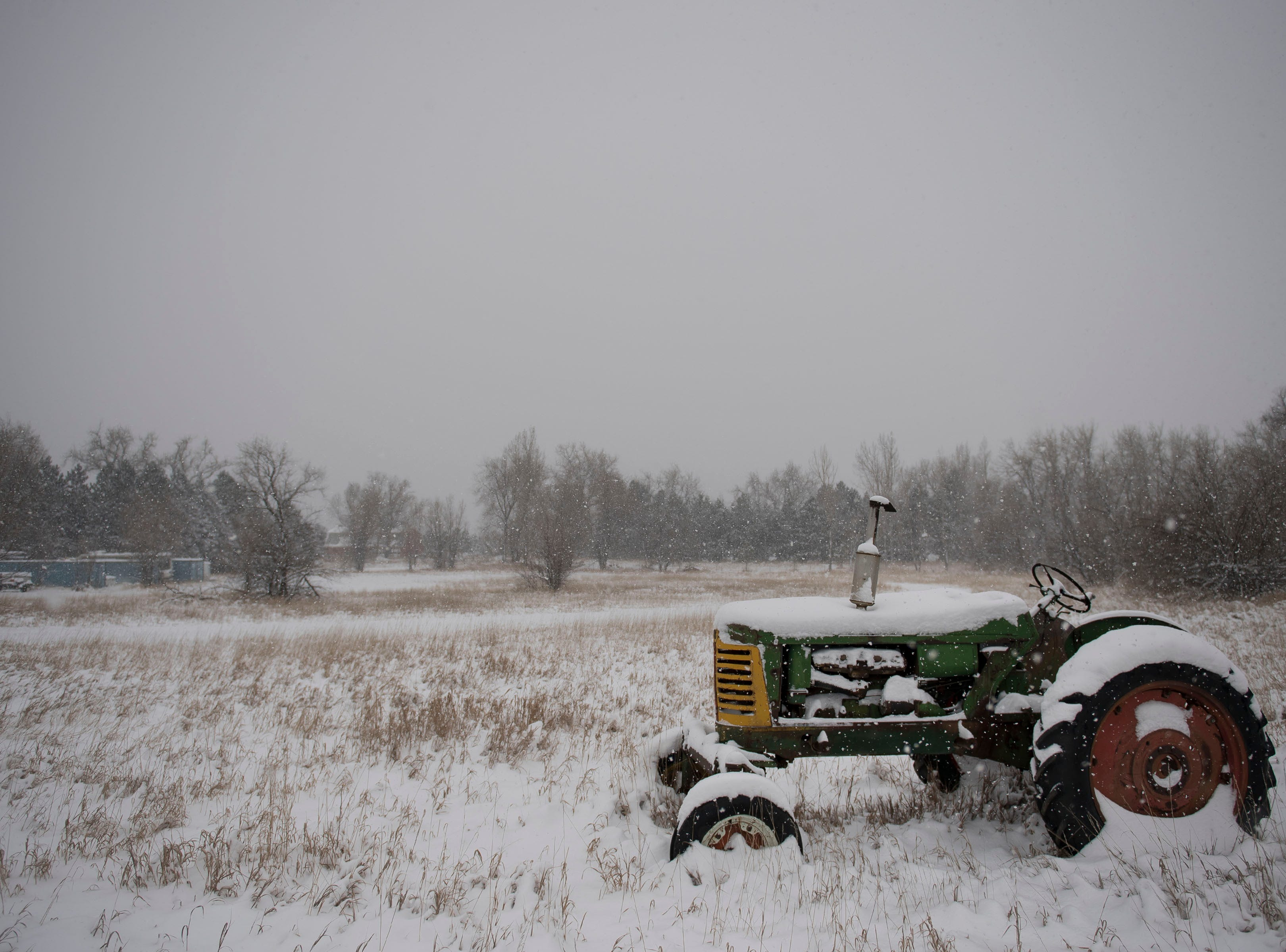 An Oliver 88 tractor sits in a field off Laporte Avenue during a snowstorm on Saturday, March 2, 2019, in Fort Collins, Colo.