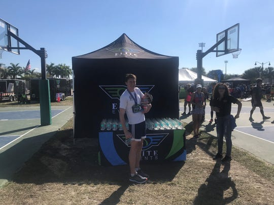 Joe Foley, of Philadelphia, poses for pictures following his first-place finish in the City of Palms Half Marathon on Saturday at Florida Gulf Coast University. Foley finished with a time of 1:18:19.