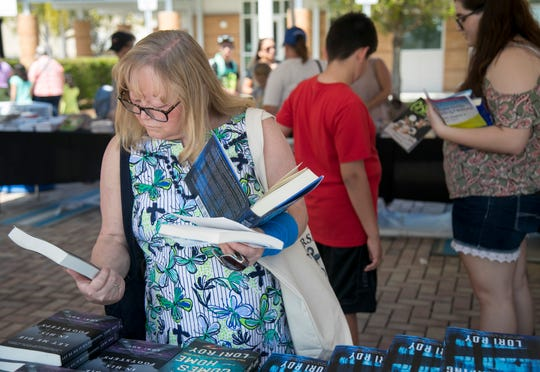 Marsha Sullivan shops for books at the Southwest Florida Reading Festival in downtown Fort Myers on Saturday, March 2, 2019.