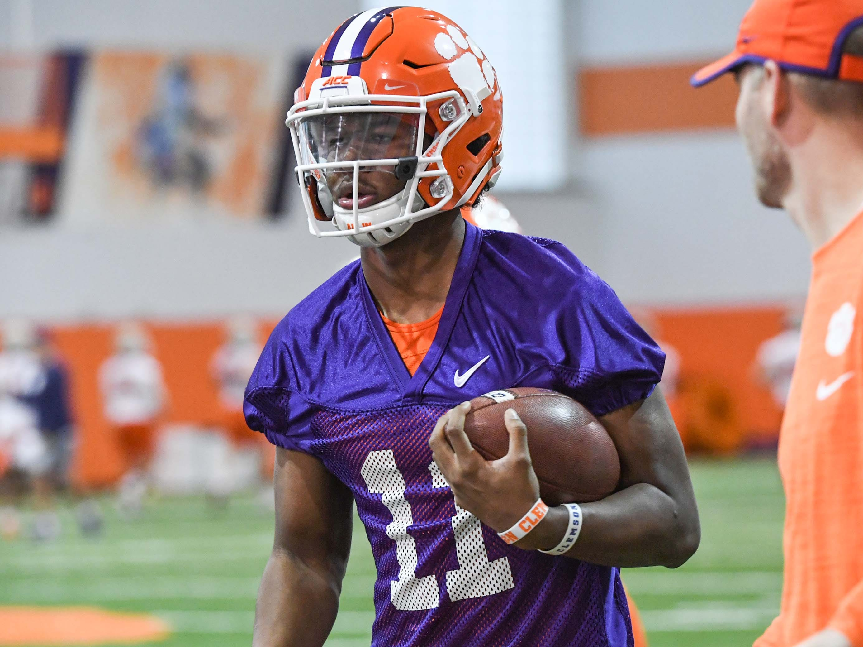 Clemson quarterback Taisun Phommachanh(11) runs by quarterbacks coach Brandon Streeter during practice at the Poe Indoor Facility in Clemson Friday.