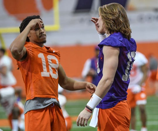 Clemson wide receiver T.J. Chase (18) greets quarterback Trevor Lawrence (16) during practice at the Poe Indoor Facility in Clemson Friday.