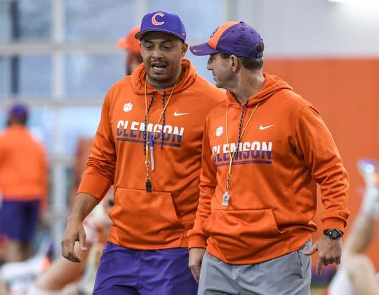 Clemson co-offensive coordinator Tony Elliott, left talks with head coach Dabo Swinney during practice at the Poe Indoor Facility in Clemson Friday.