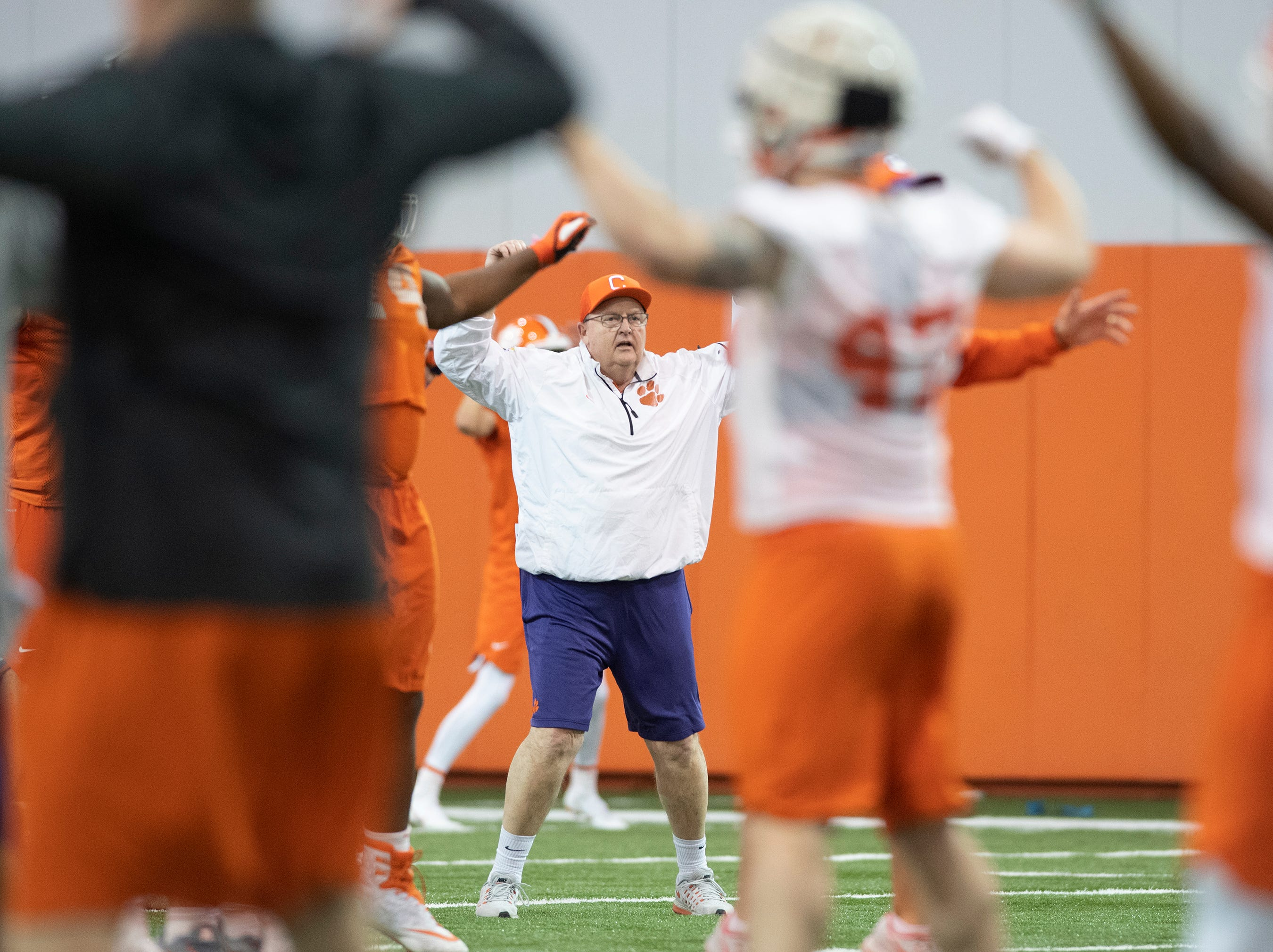 Clemson assistant coach Robbie Caldwell does jumping jacks with the team during football practice at the Poe Indoor Football Facility Friday, Mar. 1, 2019.