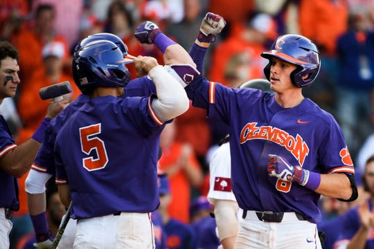 Clemson junior Logan Davidson (8) celebrates with teammates after scoring a run against South Carolina at Fluor Field Saturday, March 2, 2019.