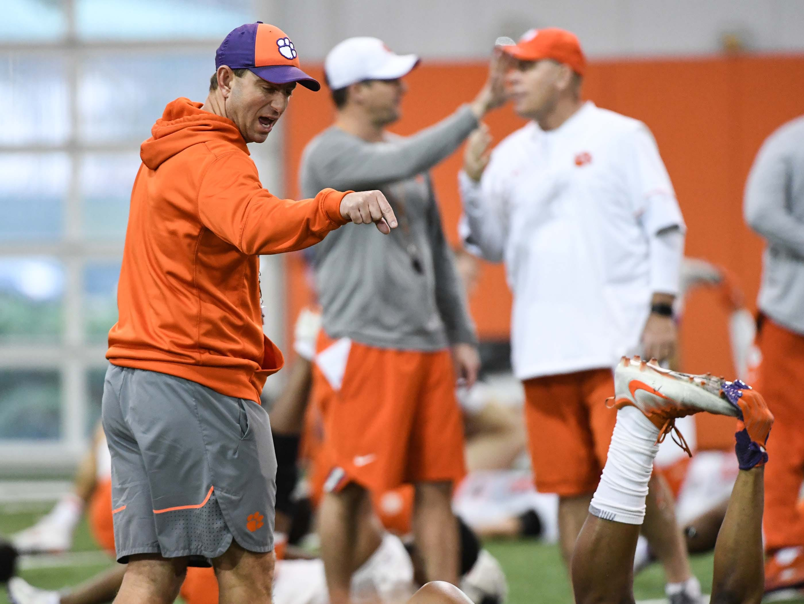 Clemson Head Coach Dabo Swinney talks with players during practice at the Poe Indoor Facility in Clemson Friday.