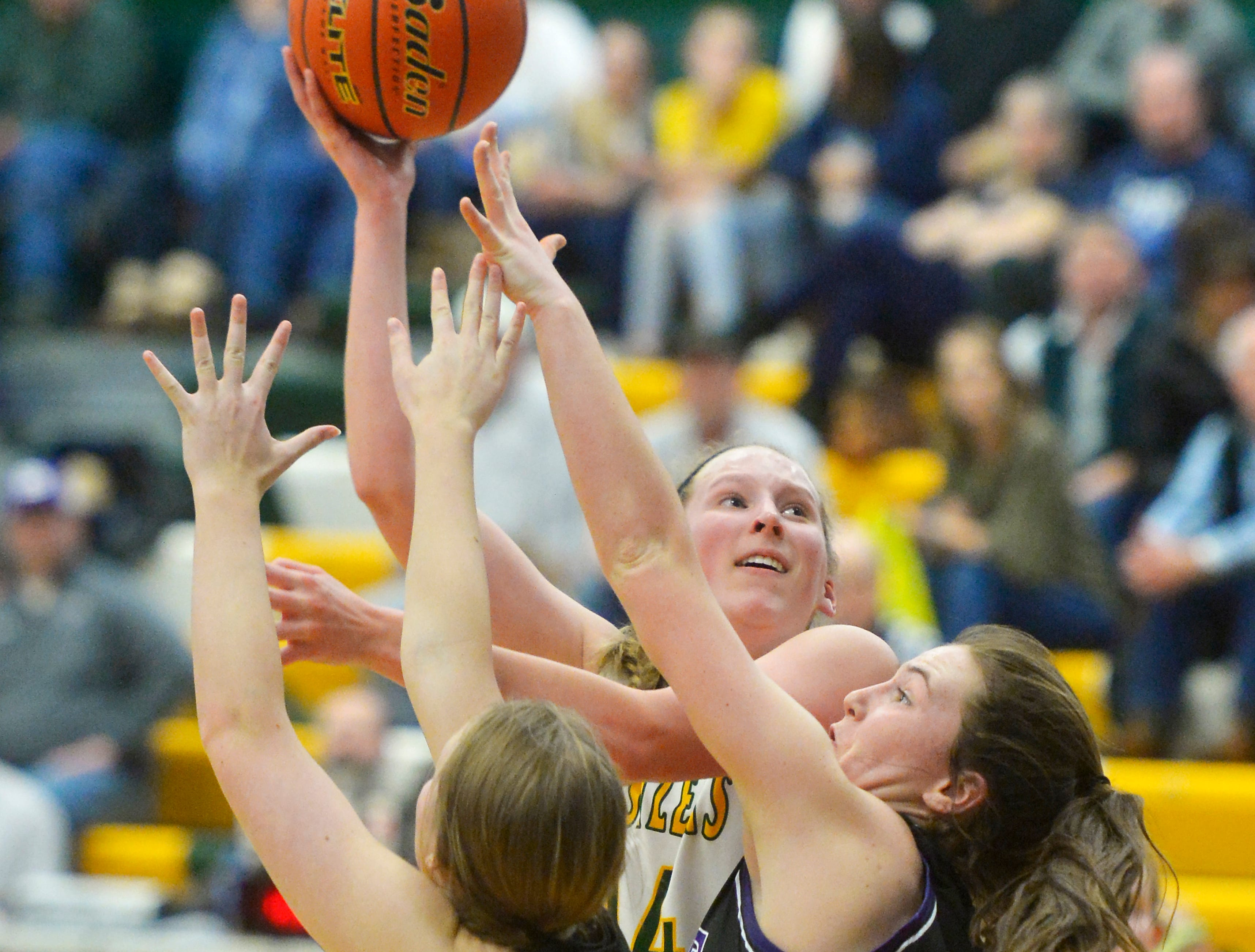 CMR's Allie Olsen attmepts a hook shot over Butte's Justise Birkenbuel and Haley Herron during the girls semifinal game of the Eastern AA Basketball Tournament at the CMR Fieldhouse, Friday.