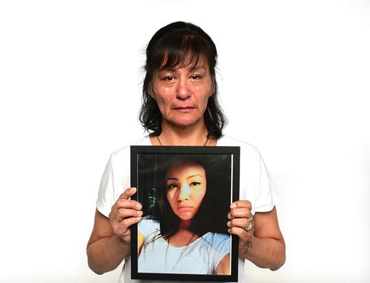 In this undated photo, Tamera Bearcomesout cries while holding a portrait of her missing daughter Shacaiah Harding, in Montana. Native American women go missing at a vastly disproportionate rate than the general population in Montana. (Larry Mayer/The Billings Gazette via AP)