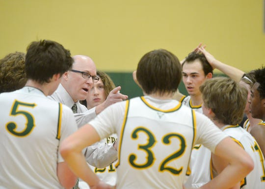 CMR's coach John Cislo huddles with his team during the semifinal game of the Eastern AA Basketball Tournament against Great Falls High, Friday.