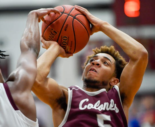 Henderson's Edmund Brooks (5) is fouled by Madisonville's Keshawn Stone (5) as the Henderson County Colonels play the Madisonville Maroons in the Boys 2nd Region basketball semi-finals Friday in Hansen, March 1, 2019.
